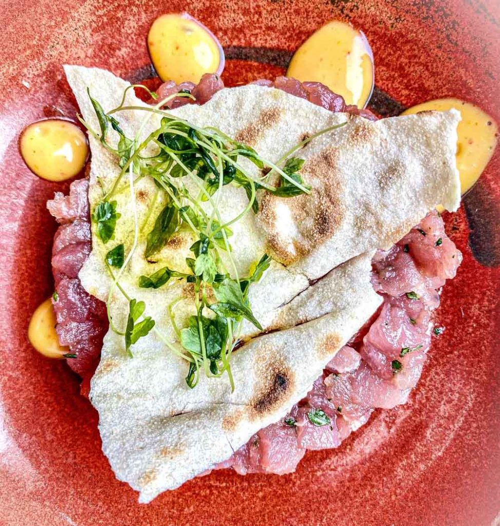 tuna tartare served with kimchi sauce and pane carasau