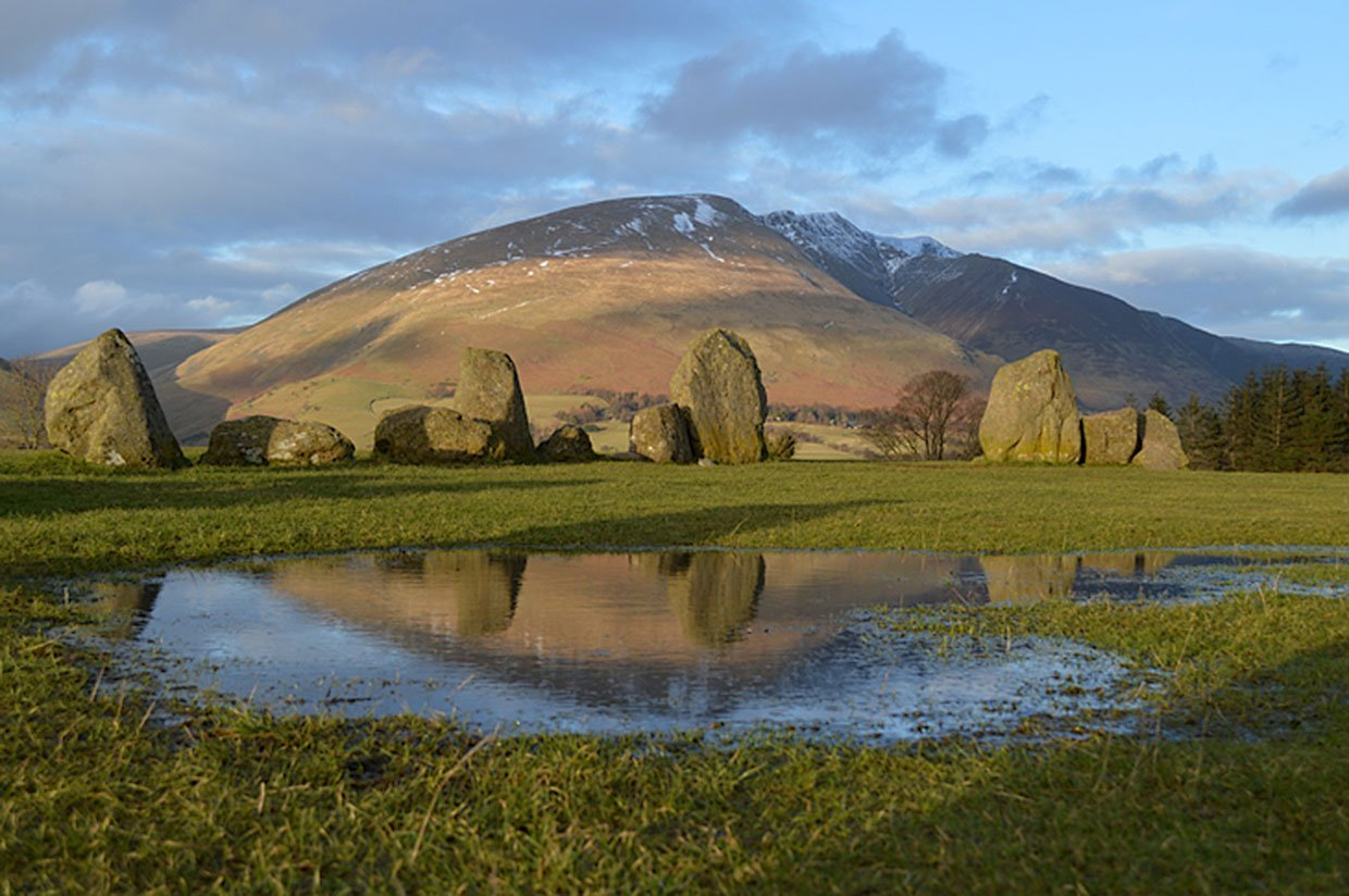 stone circle reflected in a puddle with mountain