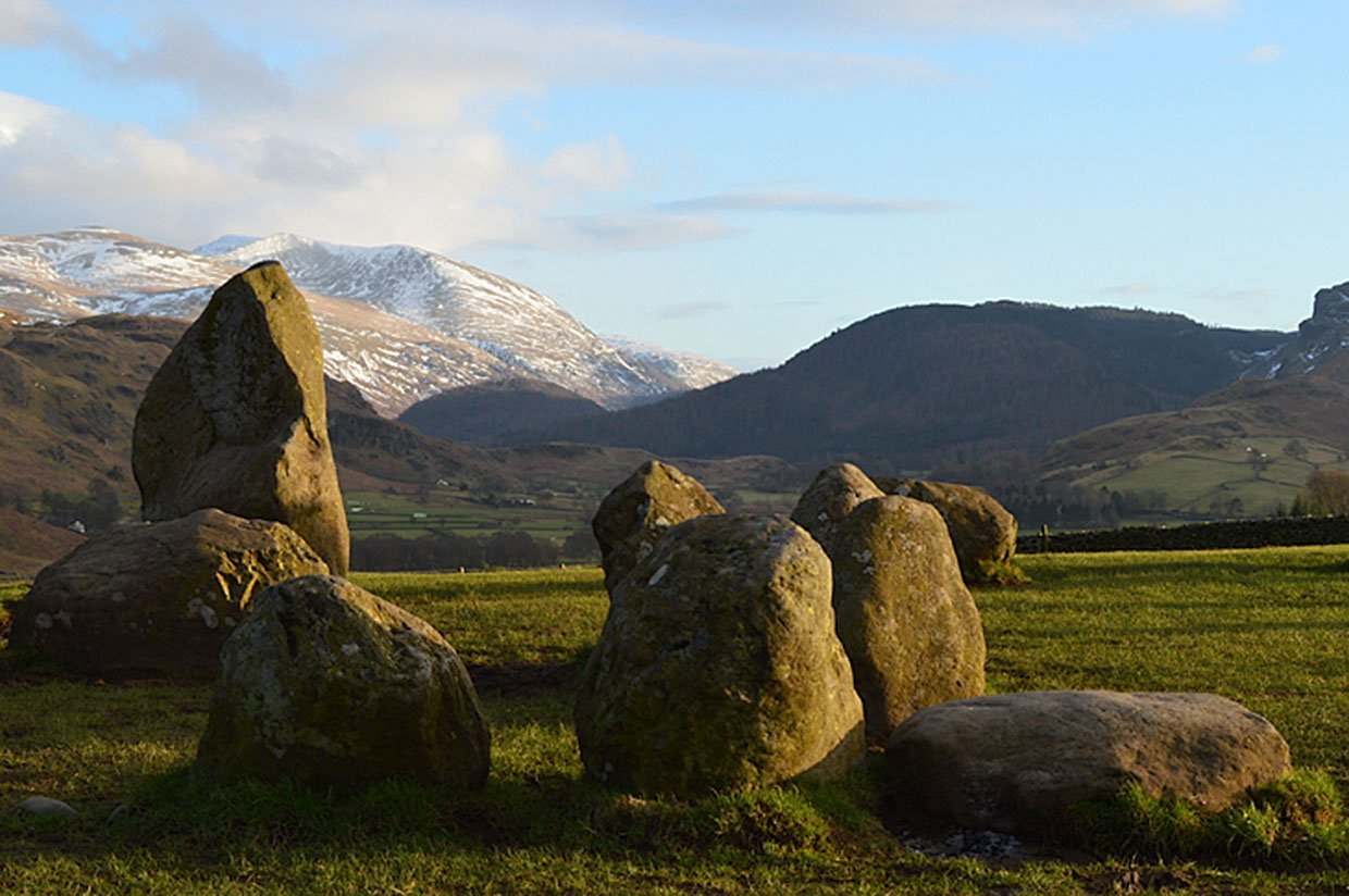 snow on the mountains behind the stones