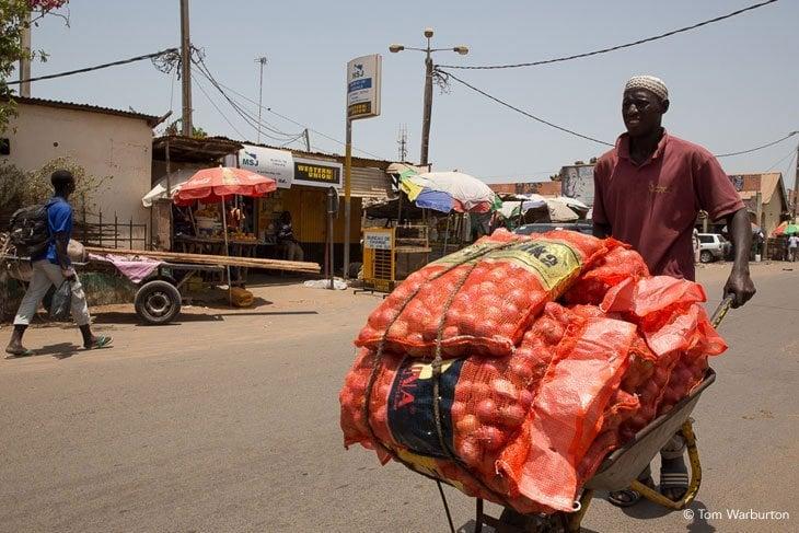 man pushing vegetables on a wheelbarrow to market