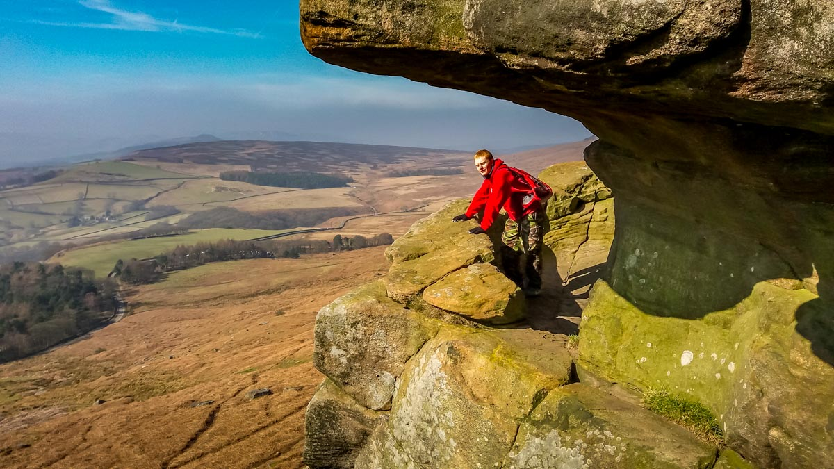 The-eldest-son-looking-out-of-Robin-Hoods-cave_ Stanage Edge and Robin Hoods Cave – A Stroll in the Peak District