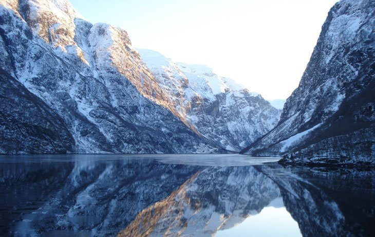 reflections of mountains in fjord